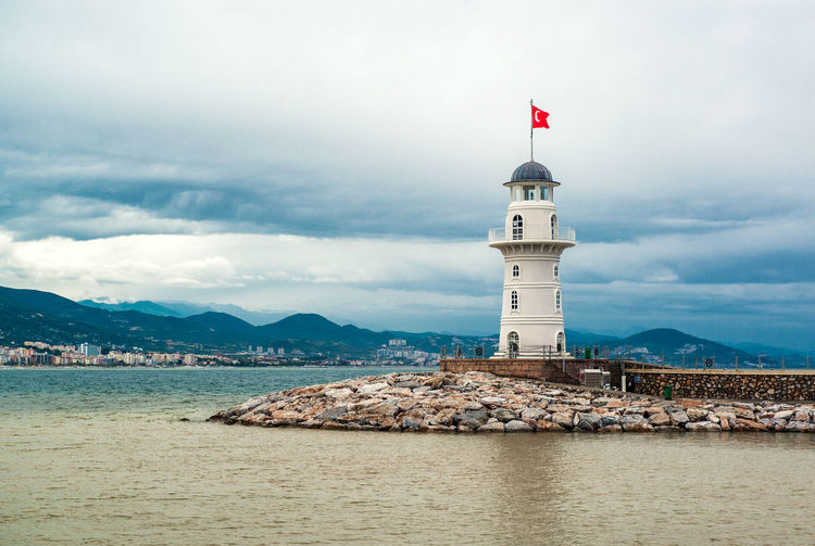 Turkish Flag On Lighthouse By Sea Against Cloudy Sky