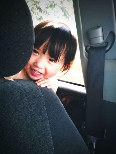 Smiling girl sitting behind seat in car