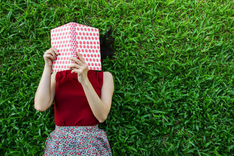Directly Above Shot Of Woman Reading Book While Lying On Grass