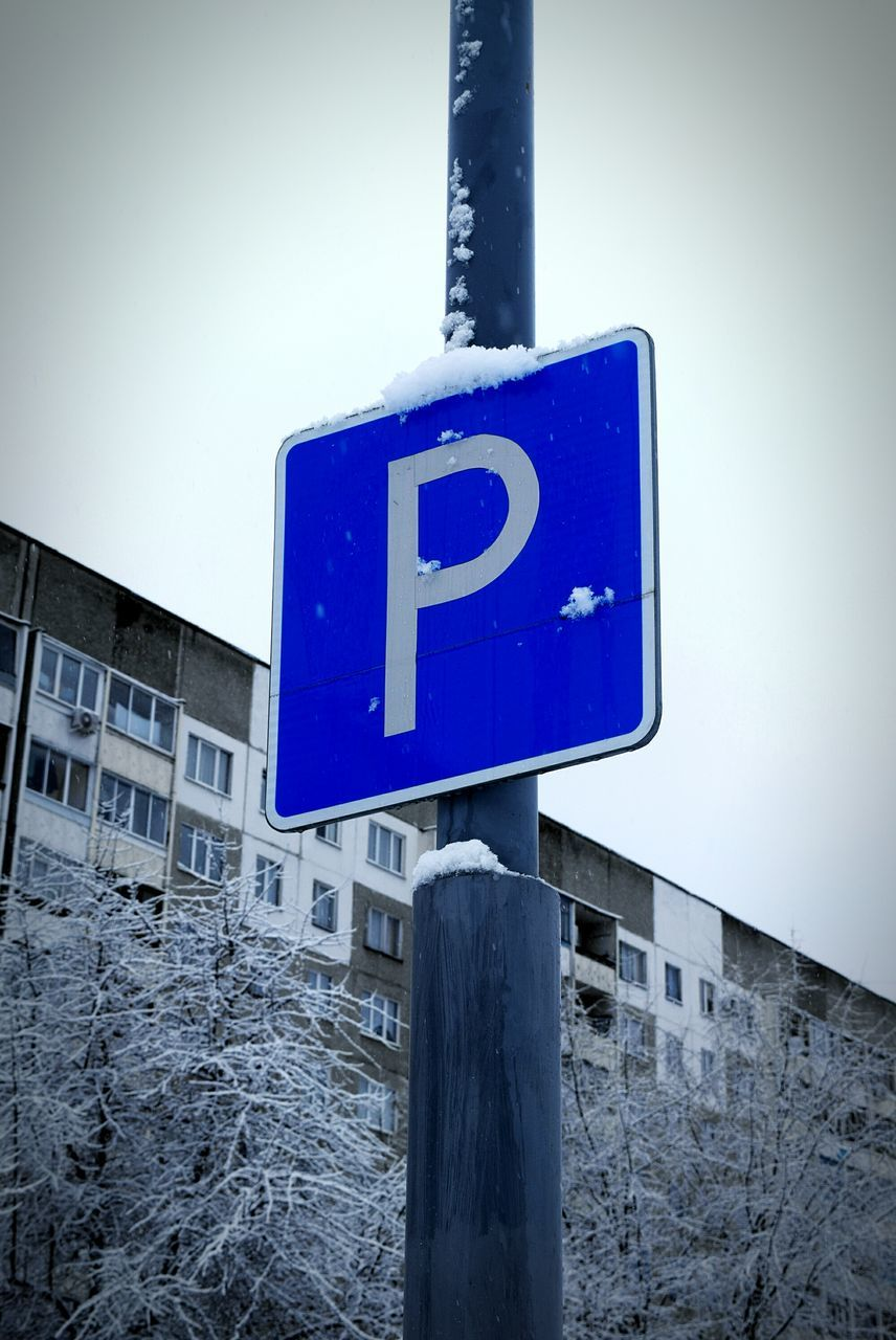 Low Angle View Of Parking Sign Against Sky During Winter