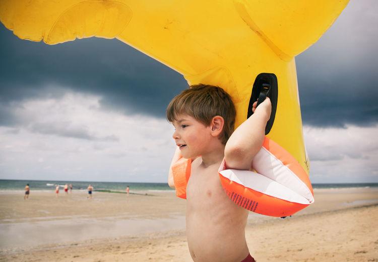Boy standing on beach against sky