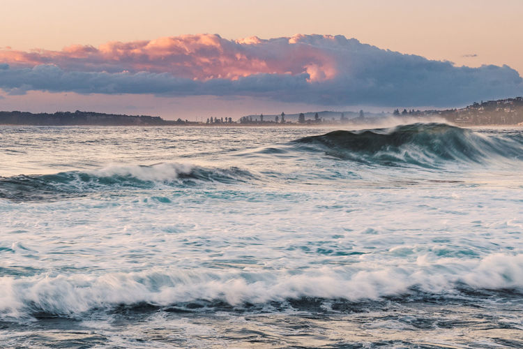 Waves breaking in sea against sky during sunset