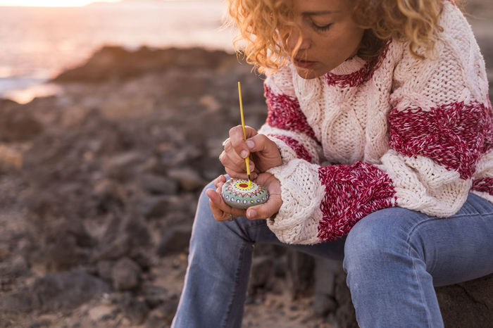 young woman curly hair sitting close the sea in relaxed moment vintage dressing Beach Blond Hair Concentration Curly Hair Day Front View Girls Holding Leisure Activity Mandala Nature One Person Outdoors Painting People Real People Relaxed Moments Rock Beach Sea Sitting Sunset Vintage Dress
