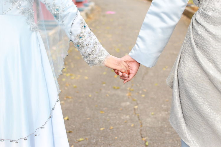 Midsection of couple with holding hands outdoors
