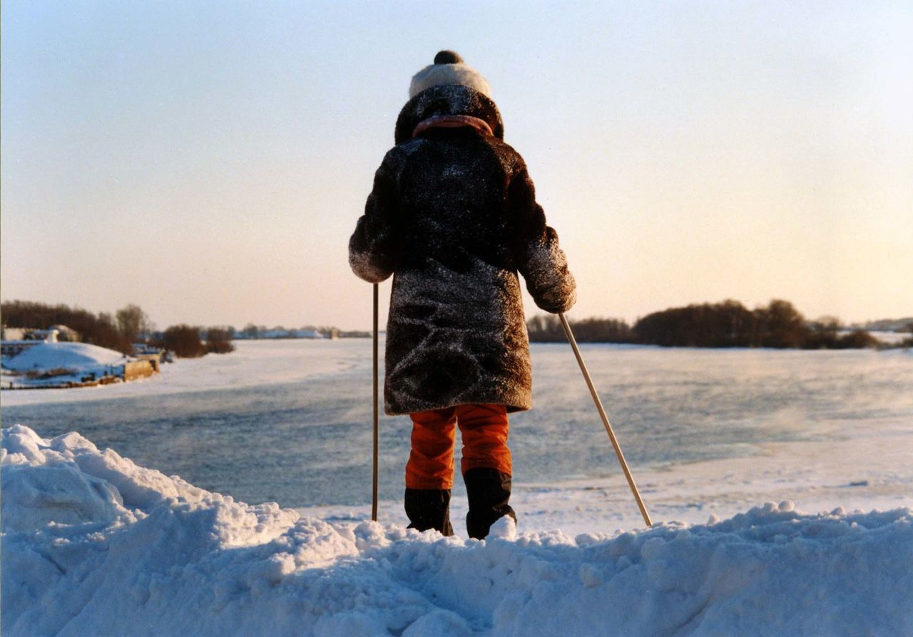 Rear view of girl standing in snow holding ski poles