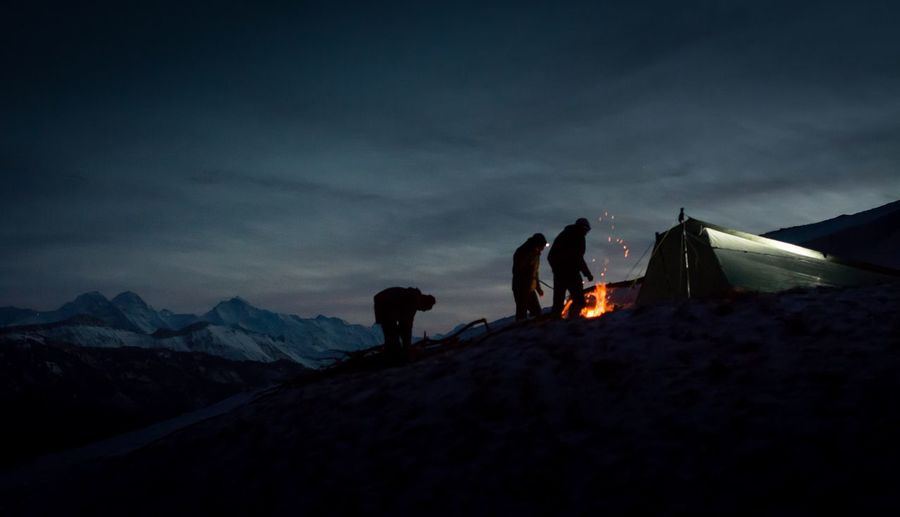 People standing by bonfire on snow covered mountain against sky