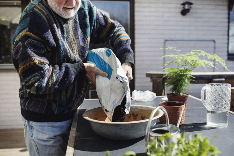 Midsection of man standing by potted plant on table