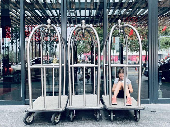 Full length of girl sitting on trolley