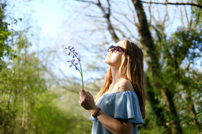 Woman wearing sunglasses standing against plants