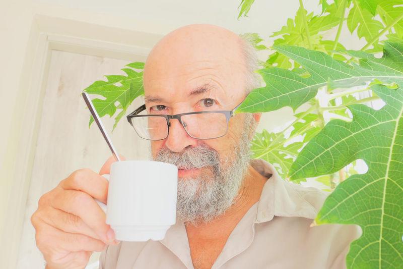 Portrait of man wearing mask holding plant