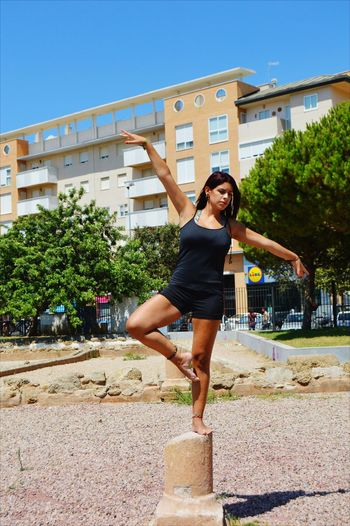 Young woman exercising on concrete pole against building