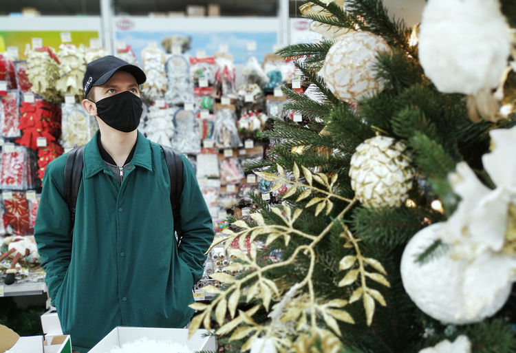 Rear view of man standing by christmas tree