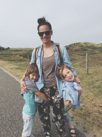 Portrait of happy woman with sons standing on road