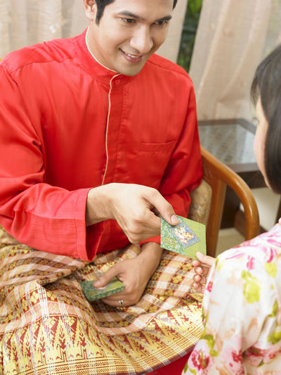 Father Giving Envelope To Daughter At Home