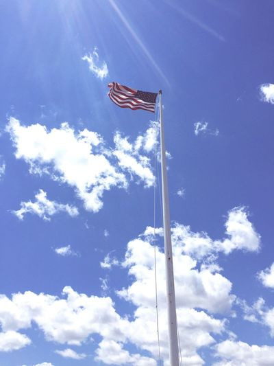 Low angle view of american flag against sky on sunny day