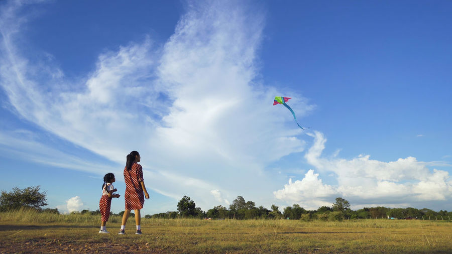Mother and daughter looking at kite against sky