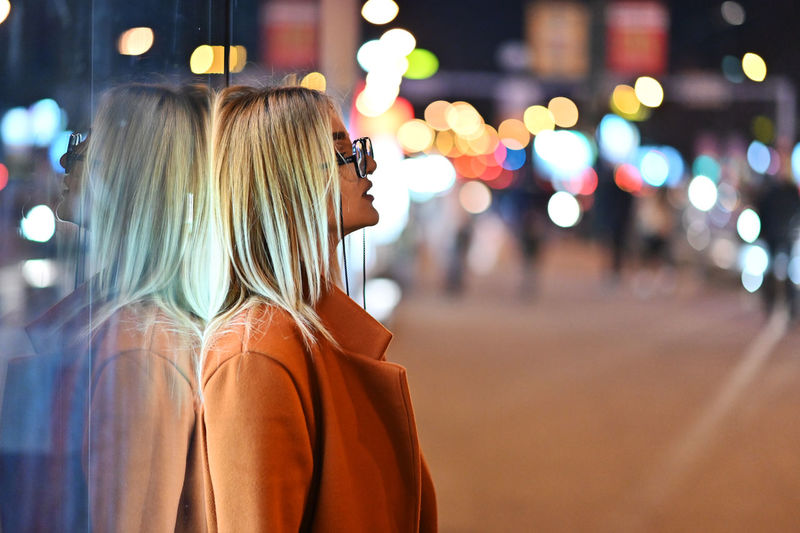 Portrait of woman standing by illuminated street at night