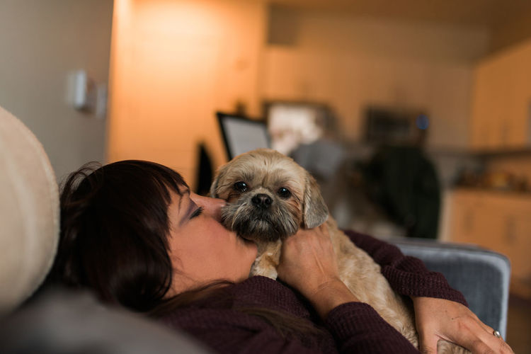 Midsection Of Woman With Dog At Home