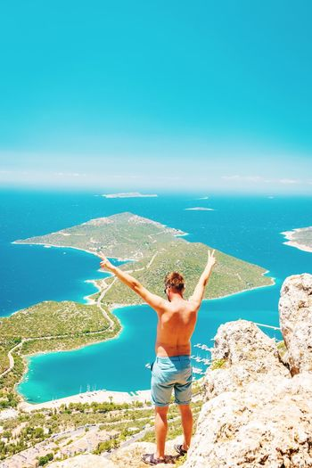 Rear View Of Shirtless Man Standing On Cliff Against Sea