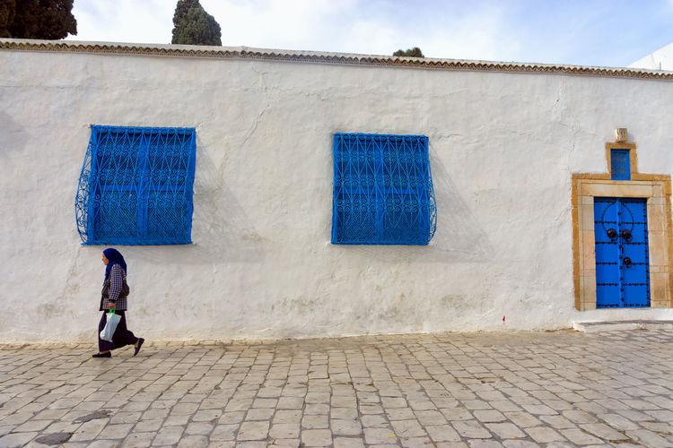 SIDI BOU SAID, TUNISIA - APRIL 3: Woman walks through one of the streets in Sidi Bou Said in Tunisia on April 3, 2018. Architecture Building Street City Outdoors Cobblestone Walking Tunisia Sidi Bou Said House Tunis Woman Africa Travel Town Mediterranean  Tourist Traditional Urban Tourism Decoration Door Muslim Arabic Landmark