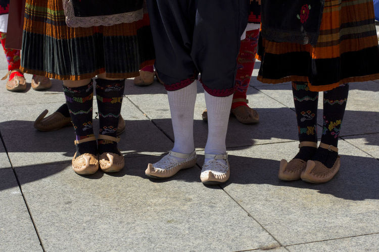 Low section of people in traditional clothing standing on footpath