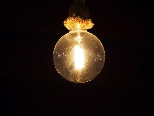 an old vintage edison lightbulb glowing against a black background Edison Bulb Lightbulb Illuminated Black Background Studio Shot Single Object Electricity  Copy Space Lighting Equipment Light Bulb Glowing Close-up Dark Luminosity Vintage