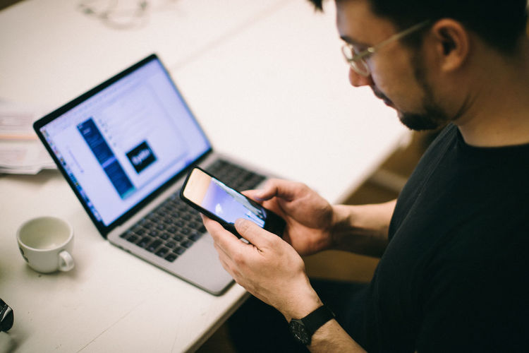 Midsection of man using laptop on table