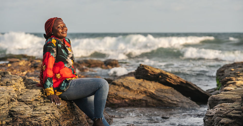 Woman sitting on rock at sea shore against sky