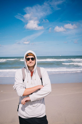 Portrait of man wearing sunglasses standing at beach against sky