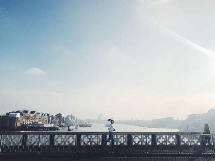 Runner on bridge over river in city against sky