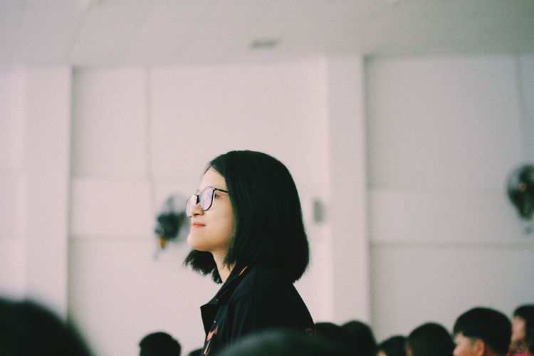 Side View Of Woman Wearing Eyeglasses While Standing Against Wall