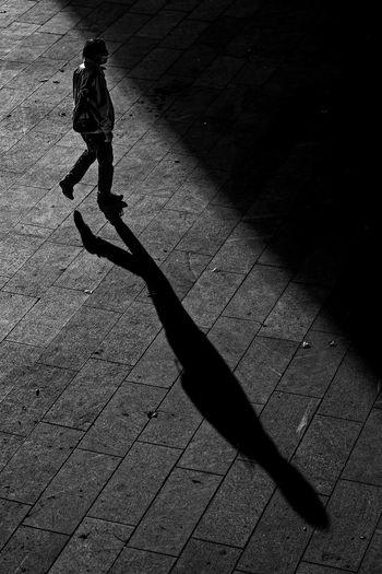 Shadow of woman walking on street