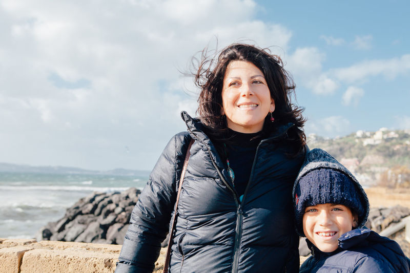Portrait of smiling boy with mother standing at beach against sky