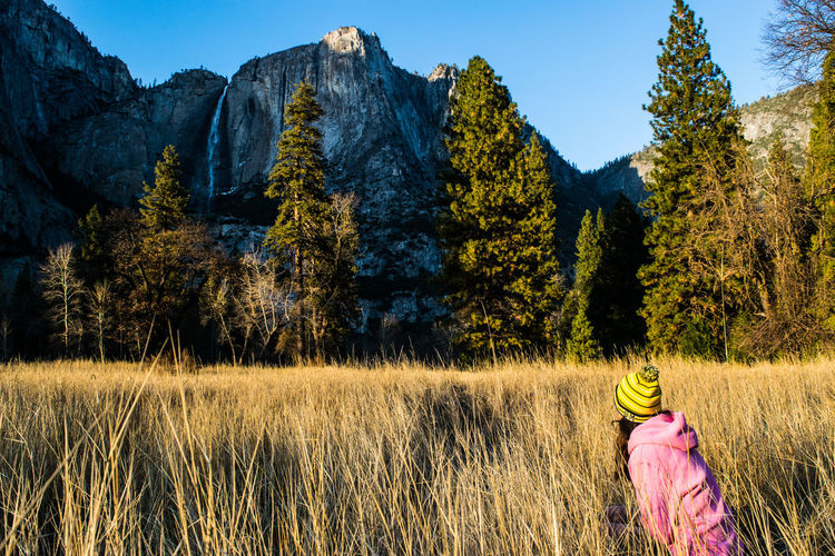 Girl on grassy field by rocky mountains