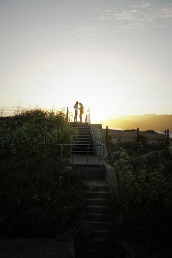 Silhouette people standing on staircase against sky during sunset