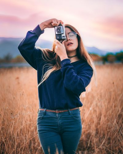 Portrait of young woman photographing on field