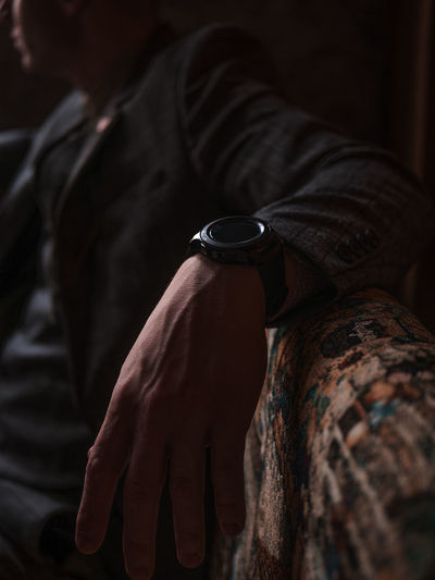Midsection of man wearing watch sitting on sofa