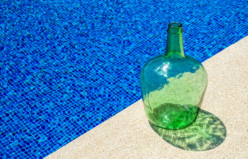 High Angle View Of Empty Glass Gallon At Poolside