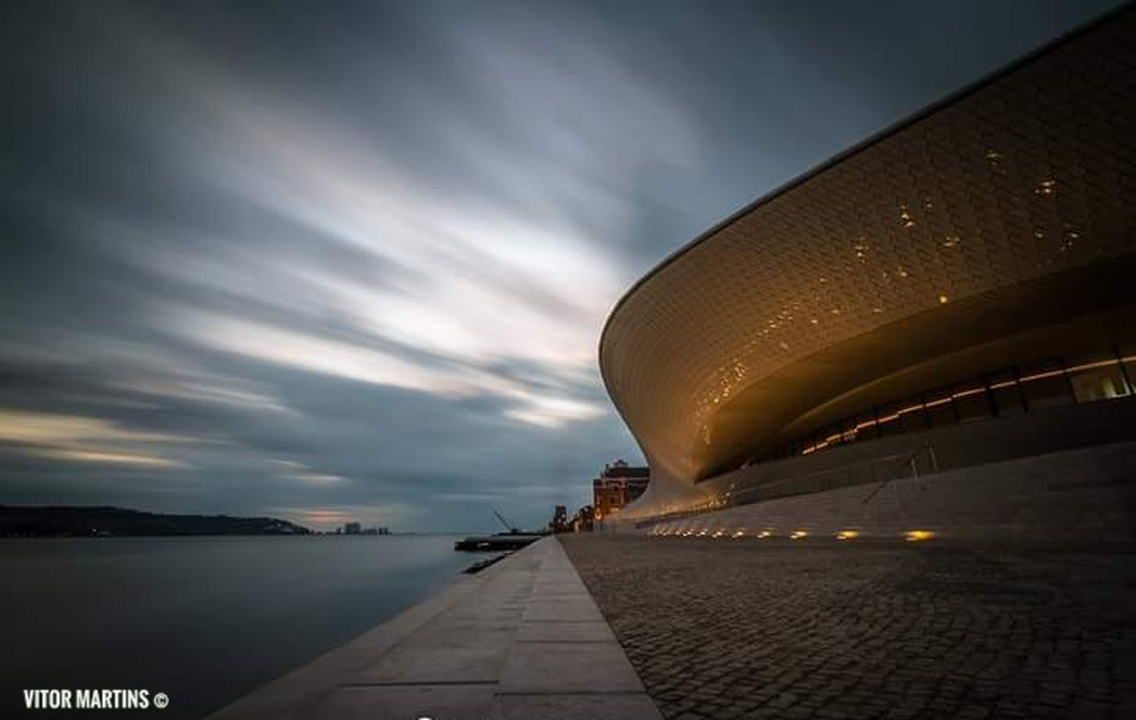 architecture, travel destinations, cloud - sky, sky, dusk, travel, arts culture and entertainment, illuminated, built structure, sea, outdoors, modern, building exterior, sunset, night, concert hall, water, city, no people, close-up