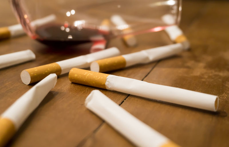 Cigarettes and a glass of red wine on a wooden table Addiction Alchohol Alcholism Cigarettes Close-up Glass Glass Of Wine Hangover Indoors  No People Party Party Is Over Red Wine Smoke Addiction Smoking Issues Table Tobacco Tobacco Addiction Wine Wooden Wooden Table