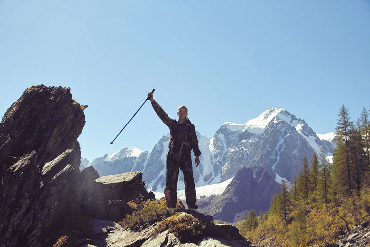 Man with arms raised holding hiking pole while standing on rock against mountains and sky