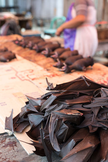 Dead bats for sell in a butcher's stall of indonesian street market. Selective focus on chopped bat wings. Choice Close-up Day Focus On Foreground Food For Sale Freshness Human Hand Large Group Of Objects Low Section Market Men Occupation One Person Outdoors Paper Real People Retail  Women