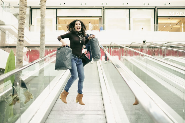 Young Woman With Shopping Bags Jumping In Mid-Air Over Moving Walkway At Shopping Mall