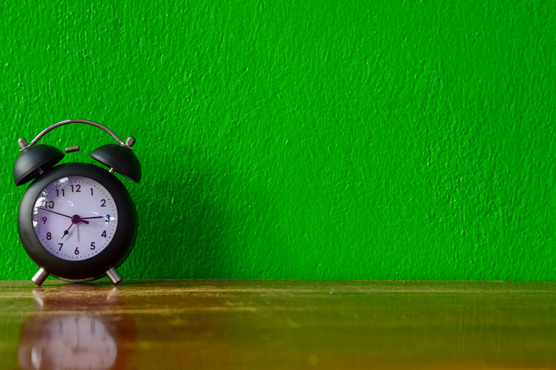 Old clock on green wall Clock Time Alarm Clock Green Color Wall - Building Feature Indoors  Still Life No People Table Number Copy Space Close-up Wood - Material Clock Face Deadline Single Object Instrument Of Time Day Accuracy