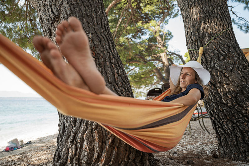 Young woman relaxing on hammock by tree