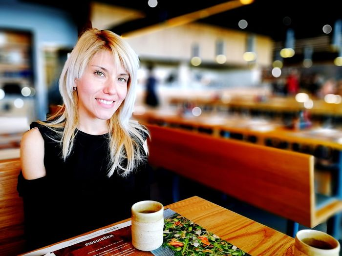 Portrait of smiling woman sitting at restaurant