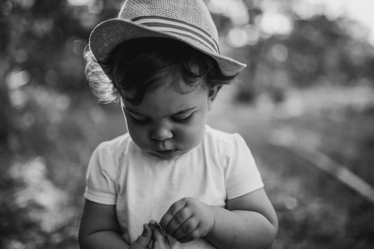 Cute baby girl wearing hat standing outdoors