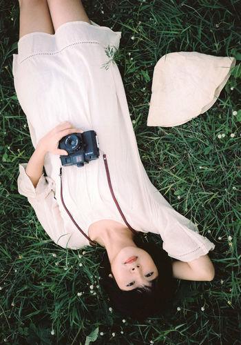 Portrait of woman lying on field