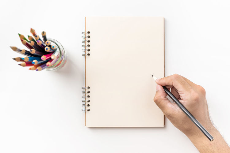 Cropped hand holding pencil on spiral notebook against white background