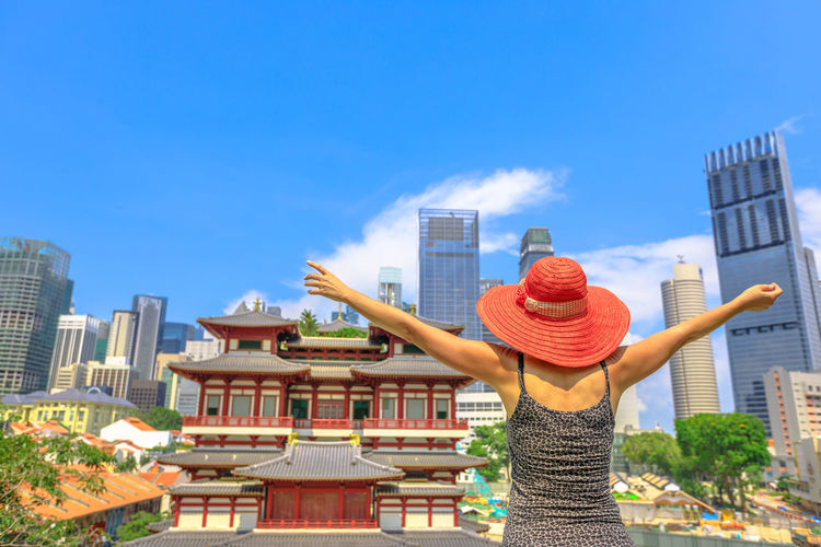 Carefree woman enjoying panoramic views of famous Buddha Tooth Relic Temple in heart of Chinatown, Singapore. Aerial cityscape skyline downtown. Lifestyle tourist with raised arms in a sunny blue sky. Singapore Singapore City Woman Tourist Tourist Attraction  Tourist Destination People Girl Females Aerial View Skyline Cityscape Panorama Happy Travel Hat Lifestyle Enjoy Nature Tourism Buddha Tooth Relic Temple, Singapore Buddha Tooth Relic Temple Temple Buddhist Temple Buddhism Building Exterior Architecture Built Structure Sky City Building One Person Day Lifestyles Rear View Leisure Activity Women Real People Three Quarter Length Standing Adult Human Arm Spirituality Outdoors Office Building Exterior Arms Raised Skyscraper
